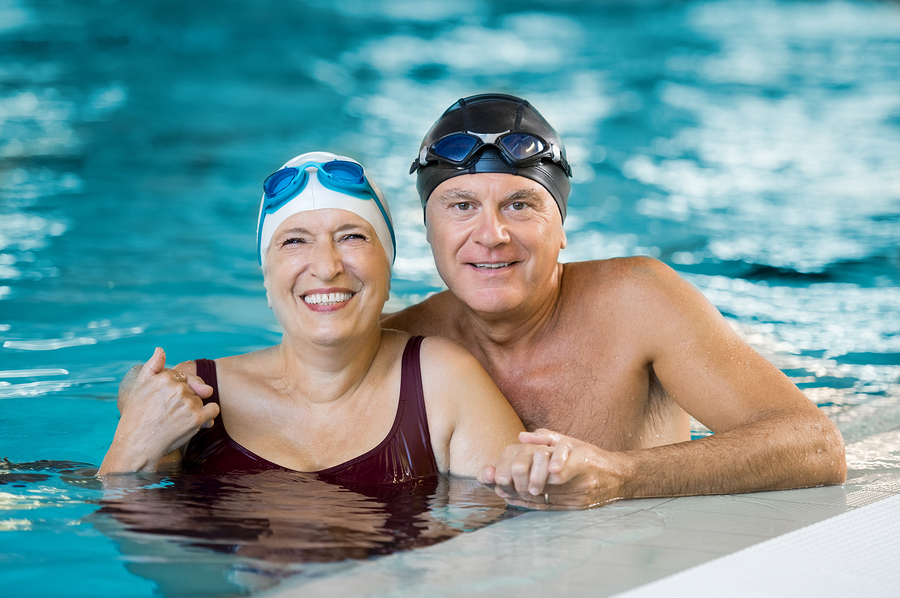 Portrait of a senior couple bathing in swimming pool and looking