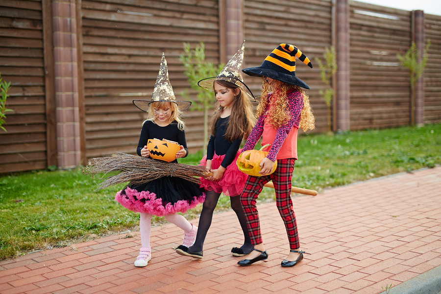 Little halloween witches in hats trick-or-treating